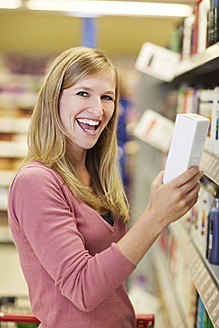 Germany, Cologne, Young woman in supermarket, smiling, portrait - RKNF000046