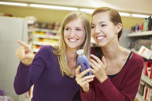 Germany, Cologne, Young women in supermarket, smiling - RKNF000057