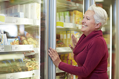 Germany, Cologne, Mature woman standing at freezer in supermarket - RKNF000080