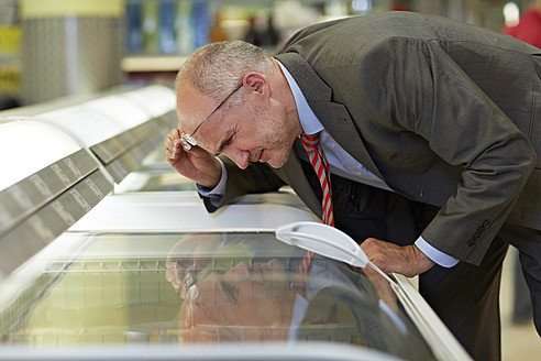Germany, Cologne, Mature man looking at freezer in supermarket - RKNF000083