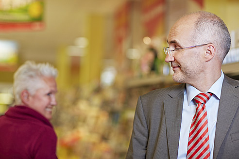 Germany, Cologne, Mature couple in supermarket, smiling - RKNF000089
