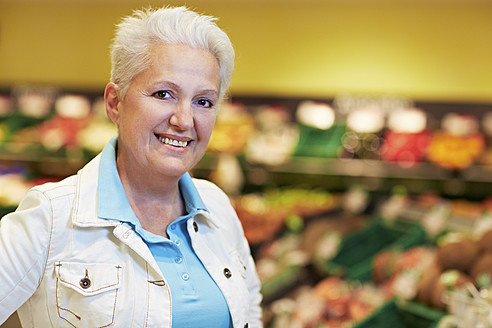 Germany, Cologne, Mature woman in supermarket, smiling, portrait - RKNF000098