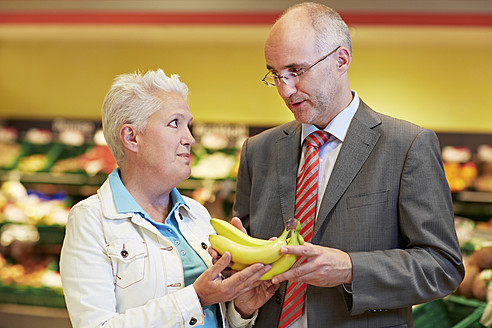 Germany, Cologne, Mature couple with bananas in supermarket - RKNF000104