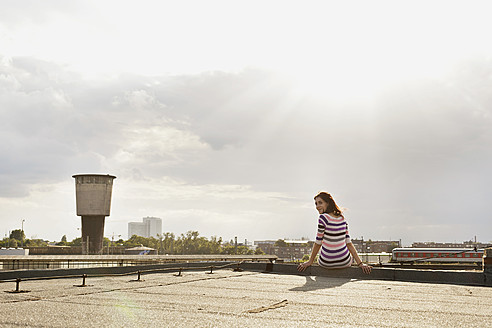 Germany, Hamburg, Young woman sitting at edge of roof - DBF000217