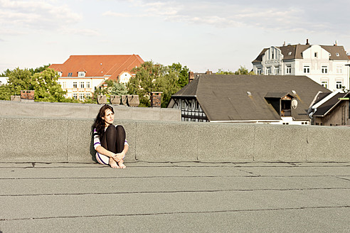 Germany, Hamburg, Young woman sitting on roof - DBF000206