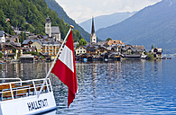 Austria, Upper Austria, Hallstatt, Boat with flag on lake, village in background - EJW000017