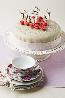Cake decorated with butterflies shaped and marzipan, cup and saucer in foreground - ECF000030