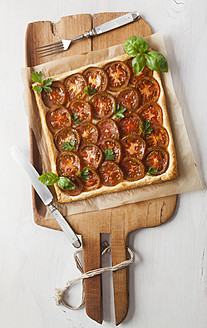 Puff pastry tarte garnished with tomato slices and herb on chopping board - ECF000070