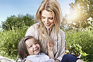 Germany, Cologne, Mother and daughter sitting on meadow, smiling - PDYF000005