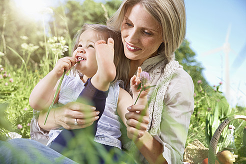 Germany, Cologne, Mother and daughter at picnic, smiling - PDYF000008