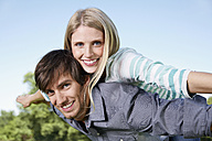 Germany, Cologne, Young couple flying, smiling, portrait - PDYF000062