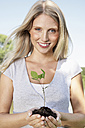 Germany, Cologne, Young woman holding seedling, smiling, portrait - PDYF000074