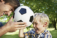 Germany, Cologne, Father and son playing with soccer ball - PDYF000104
