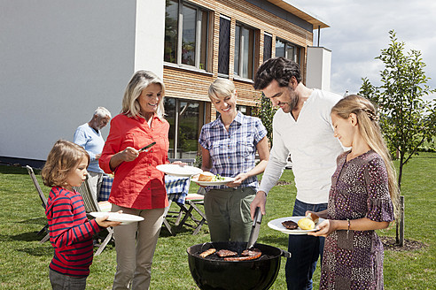 Germany, Bavaria, Nuremberg, Family standing around barbecue in garden - RBYF000125