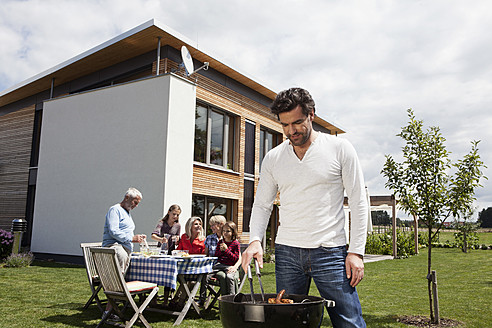 Germany, Bavaria, Nuremberg, Man cooking barbecue, family sitting in garden - RBYF000128