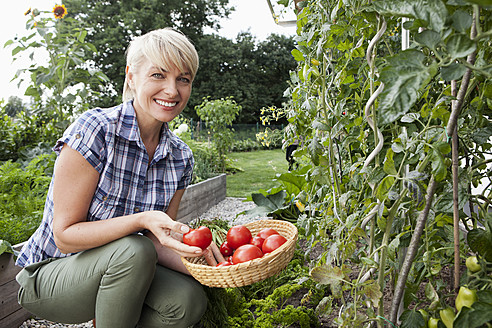 Germany, Bavaria, Nuremberg, Mature woman with vegetables in garden - RBYF000200