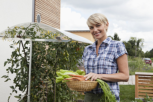 Germany, Bavaria, Nuremberg, Mature woman with vegetables in garden - RBYF000206