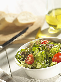 Mixed salad with bread and olive oil on table - CHF000005