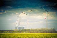 Germany, Saxony, Wind turbine with coal power plant in wind farm - MJF000125