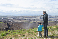 Germany, Saxony, Schleenhain, Father showing brown coal mining to son - MJ000132