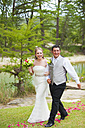 USA, Texas, Bride and groom walking on grass, smiling - ABAF000265