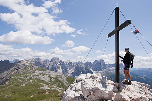 Italy, South Tyrol, Mid adult woman standing on mountain summit with cross at Mt. Petz - UMF000435