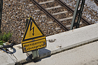 Germany, Bavaria, High voltage sign on railway track - AXF000244