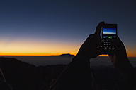 Indonesia, Human hand taking photo of sunrise - MBEF000531