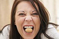 Germany, Berlin, Young woman biting walnut, close up - BFRF000006