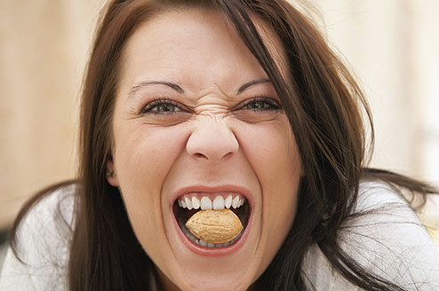 Germany, Berlin, Young woman biting walnut, close up - BFRF000006