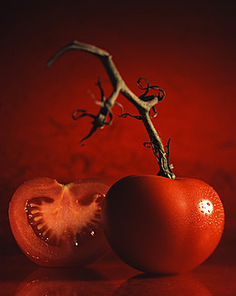 Close up of tomato with stem against red background - FKF000043
