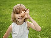 Germany, Brandenburg, Girl holding egg in front of eyes - BFRF000012
