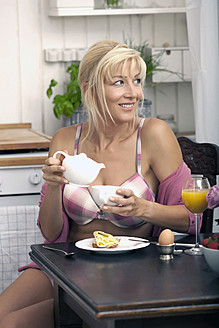 Germany, Munich, Mature woman having breakfast in kitchen - KRF000027