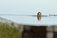 India, Kerala, Young woman relaxing in pool - MBEF000500