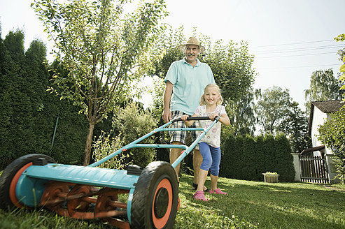 Germany, Bavaria, Grandfather with children mowing lawn - RNF001031