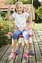 Germany, Bavaria, Girls swinging on swing, smiling, portrait - RNF001034