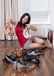 Germany, Berlin, Young woman choosing shoes - BFRF000069