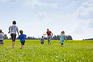 Germany, Bavaria, Group of children running through meadow - HSIYF000032