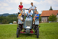 Germany, Bavaria, Woman with group of children sitting on old tractor in front of farmhouse - HSIYF000038
