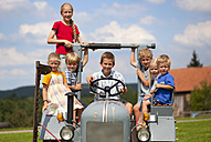 Germany, Bavaria, Group of children sitting in old tractor - HSIYF000158