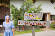 Germany, Bavaria, Mature woman standing in front of sign board - HSIYF000042