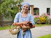 Germany, Bavaria, Mature woman with basket of fresh eggs and chicken - HSIYF000045