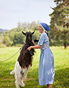 Germany, Bavaria, Mature woman playing with goat on farm - HSIYF000058