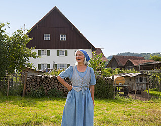 Germany, Bavaria, Mature woman standing in front of farm - HSIYF000061