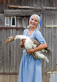 Germany, Bavaria, Mature woman with goose on farm - HSIYF000070