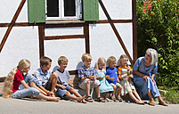 Germany, Bavaria, Woman sitting with group of children in front of small house - HSIYF000115