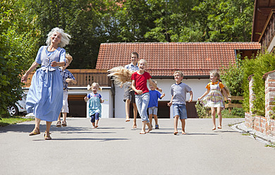 Germany, Bavaria, Woman dancing along street with group of children - HSIYF000118