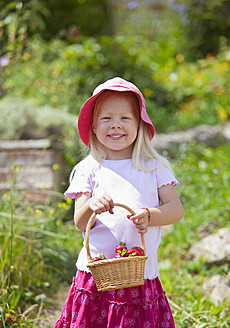 Germany, Bavaria, Girl with basket of strawberries in garden - HSIYF000120