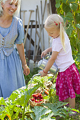 Germany, Bavaria, Mature woman and girl in graden caring for plants - HSIYF000131