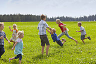 Germany, Bavaria, Group of children playing in meadow - HSIYF000137